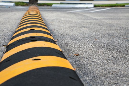 Yellow and Black Striped Speed Bump with Nails Visible in Parking Lot with Diagonal Spaces, White Blocks and Green Grass Above in Background