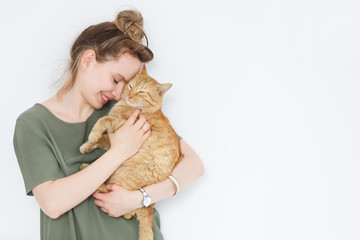 Closeup portrait handsome young hipster woman, hugs his good friend ginger cat on white wall background. Positive human emotions, facial expression, feelings. People and animals in love