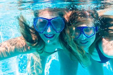 Girl friends diving underwater in resort swimming pool