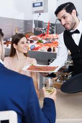 Handsome waiter bringing delicious carpaccio of raw fish