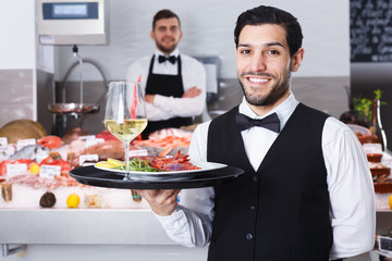 Smiling waiter holding serving tray with dishes