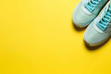 Turquoise sneakers with white soles on a yellow background close-up Wall mural