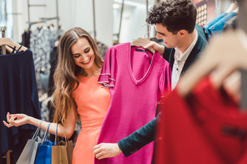 Woman with her man shopping dress in fashion store or boutique