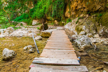 An old wooden bridge over the river at Nidri area with the waterfalls
