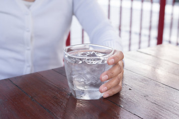 Woman holding glass of cold water.
