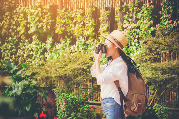 Beautiful woman taking photo tourist in flower garden