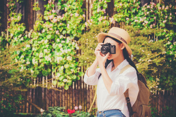 Beautiful woman taking photo tourist in flower garden