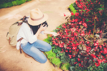 young woman taking a photo at a beautiful garden in springtime.