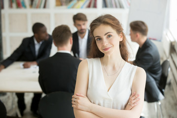 Attractive female team leader looking at camera, colleagues negotiating in background. Portrait of successful business woman posing with arms crossed. Women in business, personal achievement concept