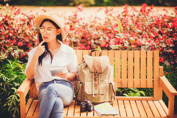 beautiful woman wearing sunglasses and hat sit on wooden chair in flower garden