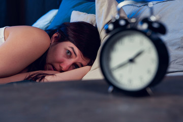 Image of brunette with insomnia lying on bed next to alarm clock at night