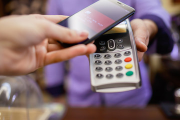 Image of buyer pays with smartphone near seller with terminal