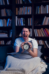 Photo of screaming man with insomnia sitting in bed with alarm clock