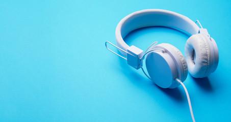 Photo of white headphones on empty blue background