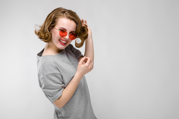 Charming young girl in a gray T-shirt on a gray background. Happy girl in red glasses. The girl is standing half-awake