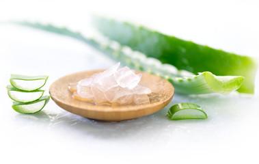 Fotoväggar - Aloe Vera gel closeup. Sliced aloevera leaf and gel, natural organic cosmetic ingredients for sensitive skin, alternative medicine. Organic Skin care concept. On white wooden background