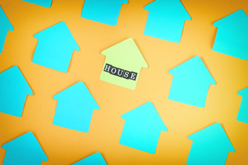Empty turquoise stickers on an orange background lie diagonally. Photo with a vignette. In the center there is a yellow sticker with the inscription HOUSE. Background with top, mock ap.