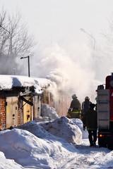 Firefighting. A fire truck and firemen at work. A lot of smoke. Winter season. Russia