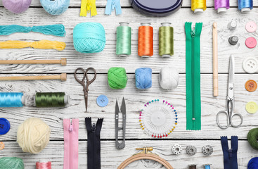 Composition with color threads and sewing accessories on wooden background, top view