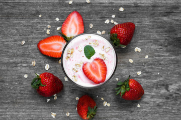 strawberry yogurt in a glass with fresh berries, oats and mint on rustic wooden background