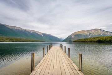 Lake Rotoiti, Tasman, Nelson Lakes, New Zealand: Beautiful scenic view to great mountain range lake with wooden jetty pier and pretty smooth reflections on the water surface at a cloudy rainy day