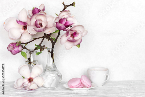 Pink magnolia flowers bouquet with coffee cup and macarons on white pink magnolia flowers bouquet with coffee cup and macarons on white wooden background mightylinksfo