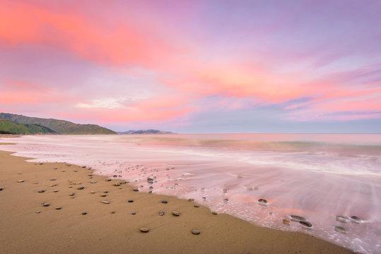 Rarangi Beach, Blenheim, Marlborough, New Zealand: Magical colorful sunset countryside with sandy beach on south island and purple pink cloudy sky and the mountain range of world famous wine region