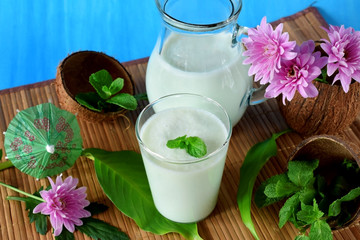 Coconut milkshake with mint flavour in a glass surrounded by coconut shells and pink flowers