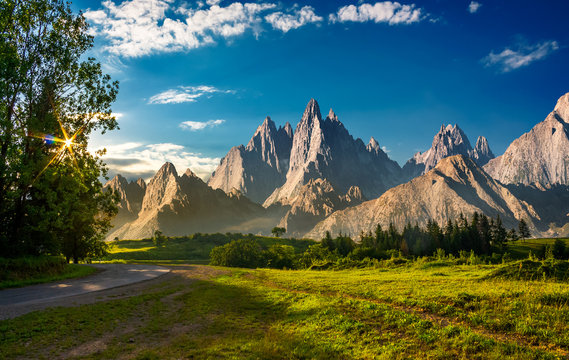 composite landscape with rocky peaks at sunset. beautiful mountainous scenery with road going through grassy hills in to the distance. sun shine through trees