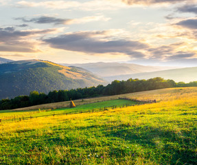 beautiful rural scenery in mountains at sunrise. haystack on the field behind the fence. outdated agriculture approach concept