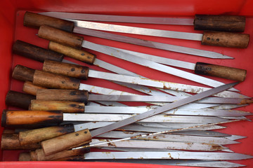 metal skewers with wooden handle in a red box after the barbecue