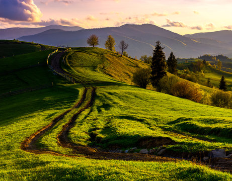 road through green hills at sunset. beautiful springtime rural landscape in mountains under the sky with pink clouds. wooden fence on top of a hill