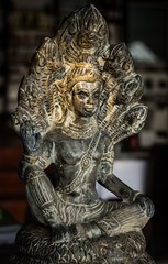 Buddha gray statue with seven head snakes naga to protect with warm sunset light on Buddha's face