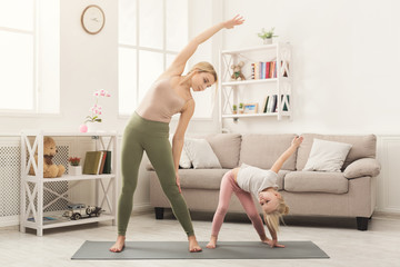 Mother and little daughter doing yoga together
