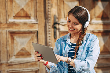 Young woman listens to music via digital tablet and headphones in the city