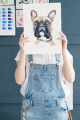 creative art lifestyle. drawing hobby and self expression. painter holding a watercolor drawing of french bulldog dog