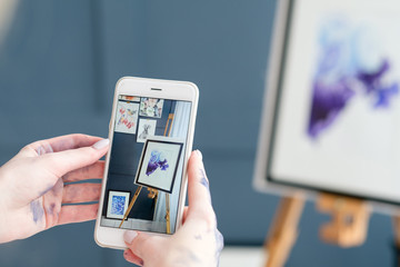 artist blogger. creativity drawing and blogging. painter takes mobile photo of her works to post online