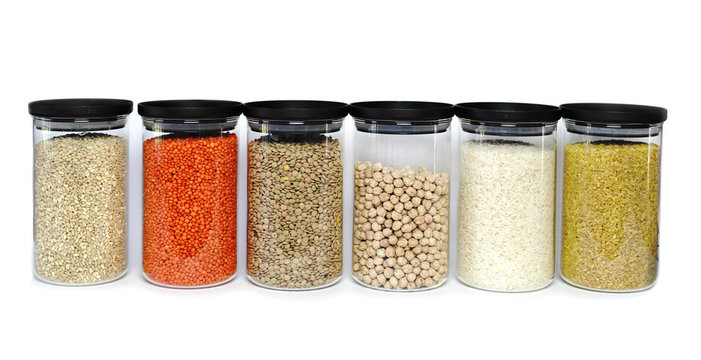 Various cerals and legumes in jars on isolated on white background.