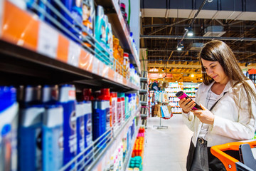 young woman in store with trolley. choose shampoo in supermarket. shopping concept. copy space