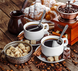 Breakfast with croissants, leaves, cutting board and black coffee composition with  wooden retro background.