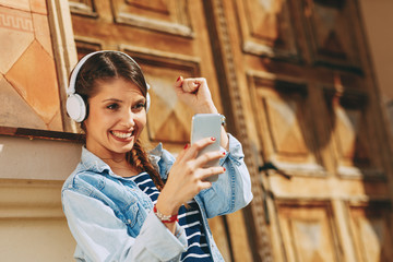 Young woman making video call via smartphone and headphones  in the city
