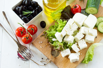 Cooking qreek salad with fresh vegetables, feta cheese and black olives on a white wooden table.