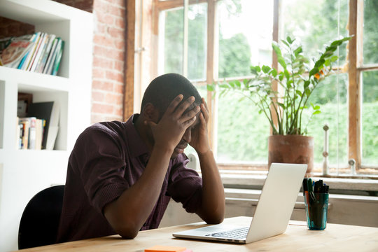 Frustrated African American worker disappointed with company business collapse, falling rates and bankruptcy news. Upset black student fail exam. Concept of failure, losing hope and stress