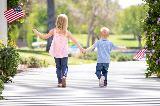 Young Sister and Brother Holding Hands and Waving American Flags At The Park