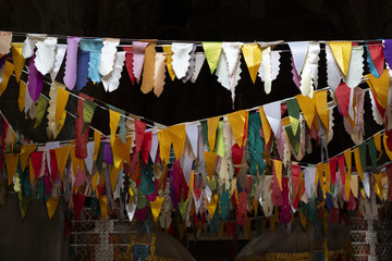 Flag banner decoration in buddhist temple. Triangle flags garland on dark background.