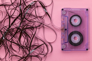 Compact audio cassette on pink background with the tangled tape hanging out