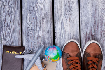 Travel concept background, flat lay. Still life with shoes, passport, toy airplane and globe.