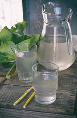 Refreshing healthy summer drink with rhubarb. Pieplant lemonade in glass on wooden background. Homemade rhabarbarum compote.