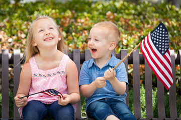 Young Sister and Brother Comparing Each Others American Flag Size On The Bench At The Park