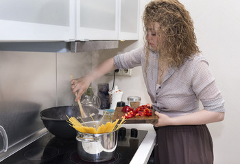 girl cooking  pasta, spaghetti cooks, holds a Board with sliced pepper, mixes the sauce, the girl prepares food in the kitchen